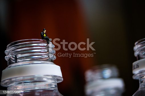 Miniature business man sitting on the plastic bottle's neck. The man in image is making a phone call with his mobile phone.