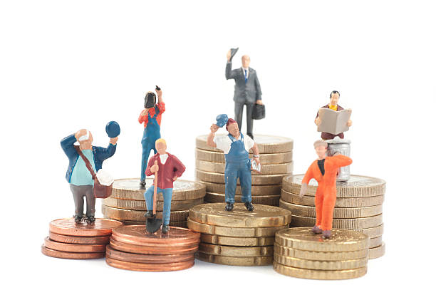 miniature business people on stacks of coins - figurine stock photos and pictures
