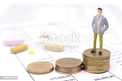 istock Miniature businessman and stack coins on statement and the drug behind. saving concept. 1008209790