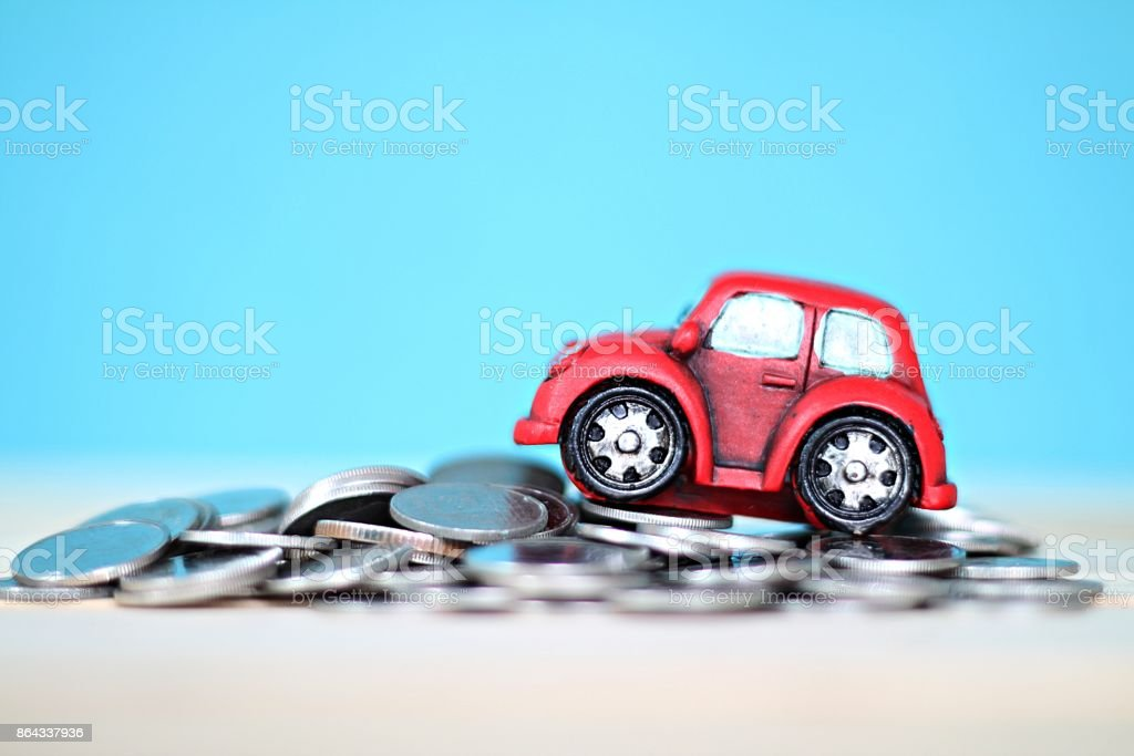 Miniature car model and coins on desk table stock photo