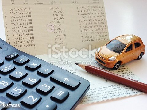 istock Miniature car model, calculator and saving account book or financial statement on office desk table 843979056