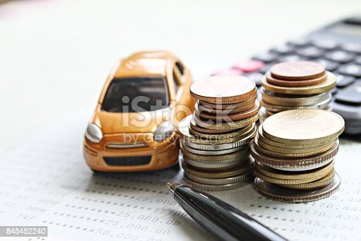 istock Miniature car model, coins stack, calculator and saving account book or financial statement on office desk table 845452240