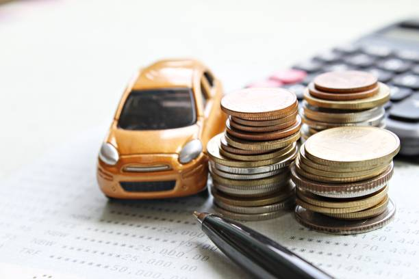 Miniature car model, coins stack, calculator and saving account book or financial statement on office desk table stock photo