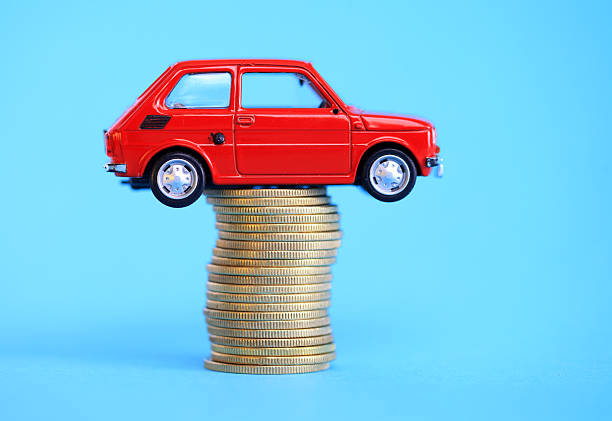 Miniature car on coin stack stock photo
