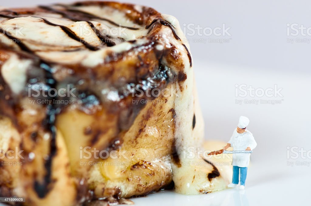 Miniature Chef with the giant Cinnamon roll Miniature Chef with the giant Cinnamon roll Adult Stock Photo