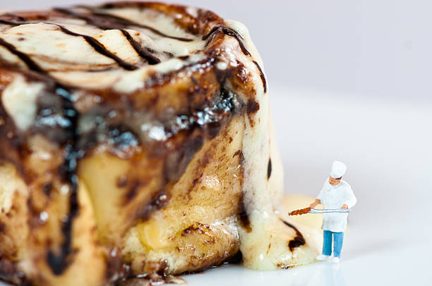 Miniature Chef with the giant Cinnamon roll stock photo