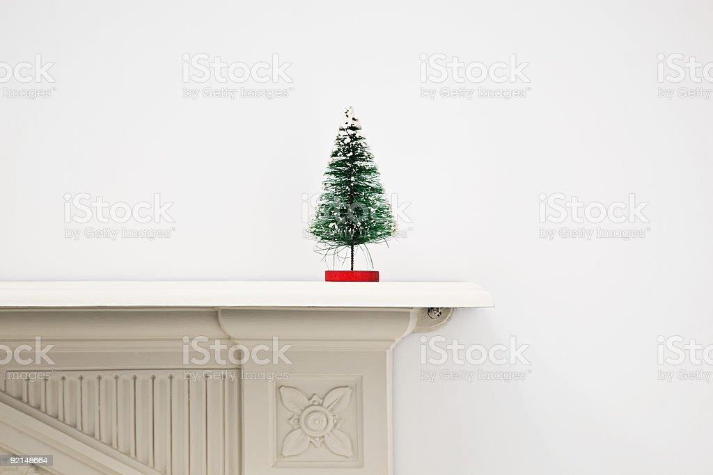 Miniature christmas tree on mantlepiece stock photo