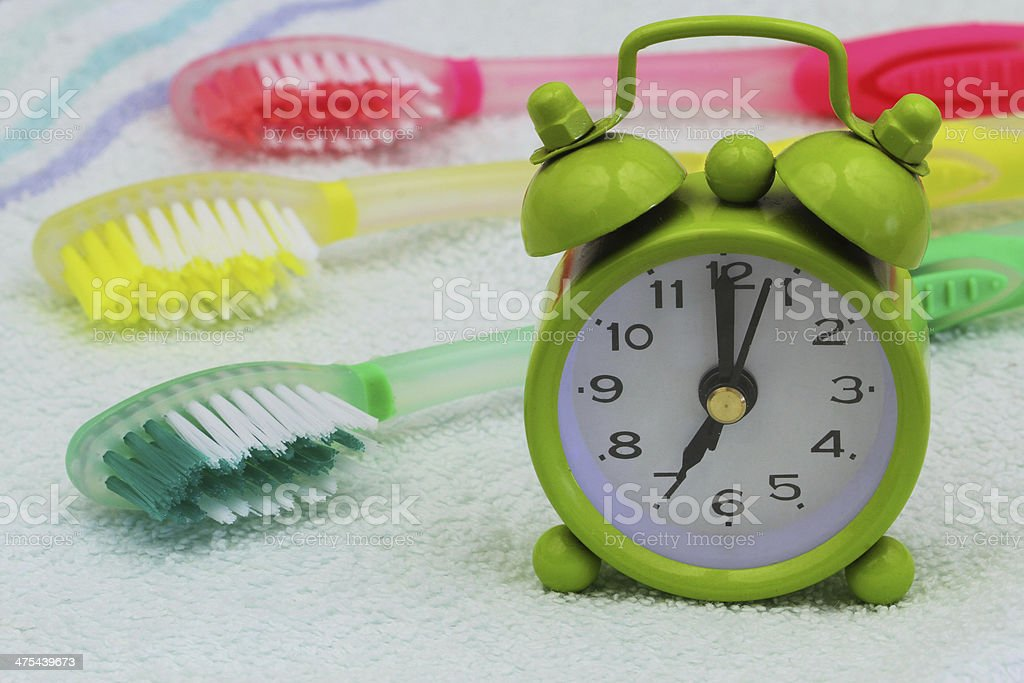 Miniature clock showing 7 am with colorful toothbrushes royalty-free stock photo