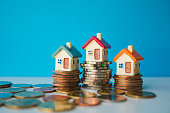 Miniature colorful house with stack coins on blue background using as property and financial concept