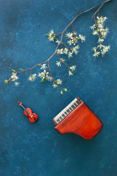 Cópias em miniatura do piano e do violino com galhos de cerejeiras florescendo. Vista superior, close-up no fundo azul clássico - foto de acervo