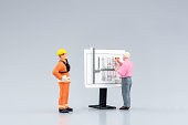 Miniature engineering people and architecture working on construction drawing