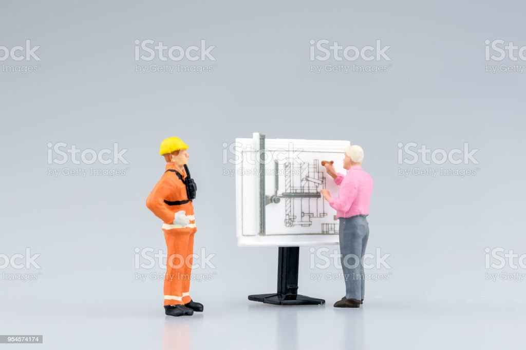 Miniature engineering people and architecture working on construction drawing stock photo