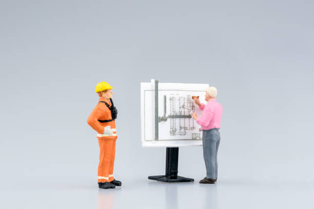 miniature engineering people and architecture working on construction drawing - figurine stock photos and pictures