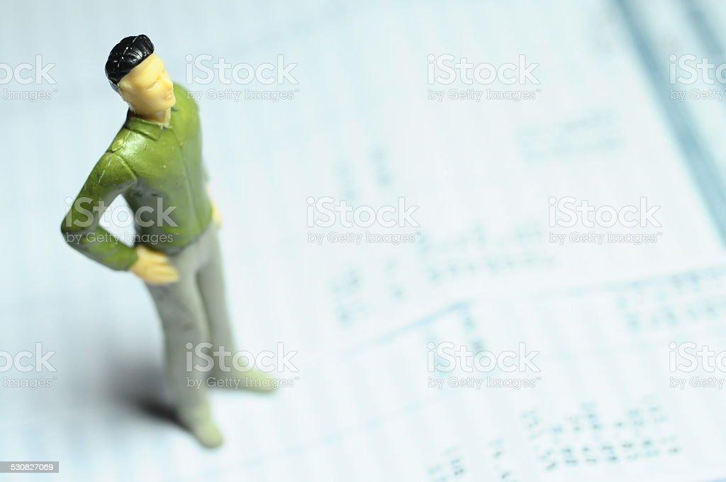Miniature figure standing on payroll stock photo