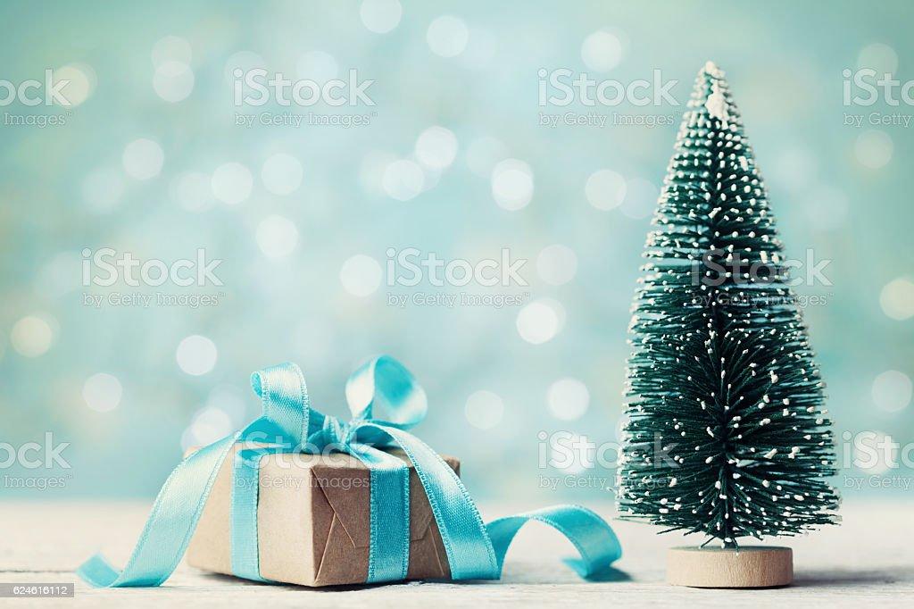 Miniature fir tree and christmas gift box. Holiday greeting card. stock photo