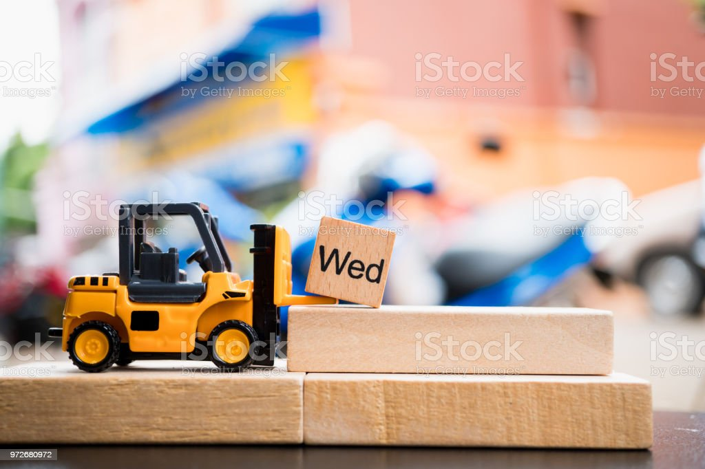 Miniature forklift lift up Wednesday wooden block stock photo