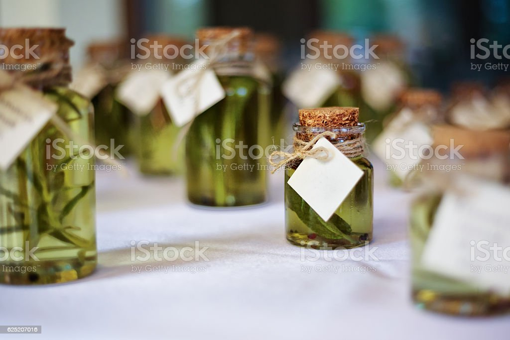 Miniature glass bottles of herb infused olive oil stock photo