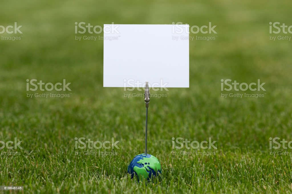 Miniature globe holding an empty white card surrounded by fresh green grass stock photo