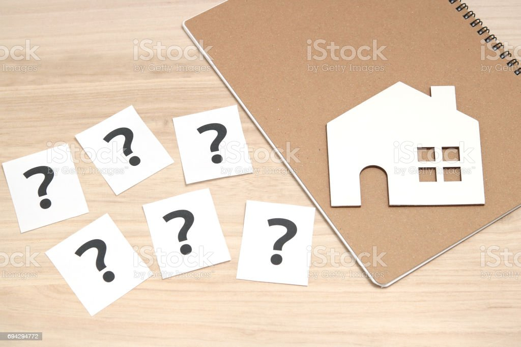 Miniature house and many question marks on white papers.   House with question marks. stock photo