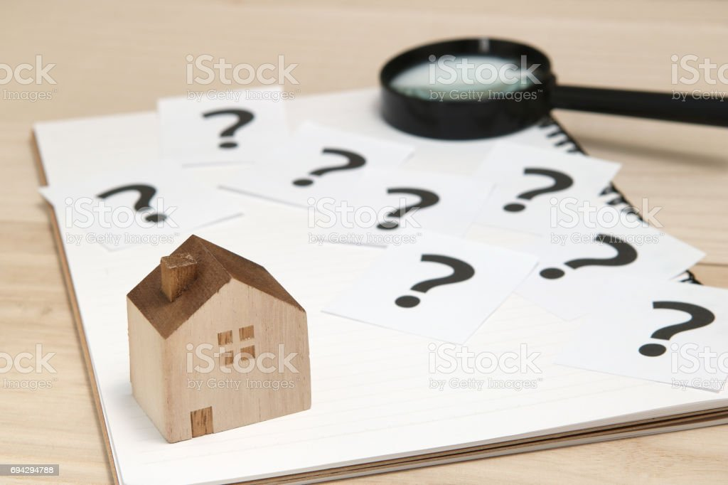 Miniature house and many question marks on white papers.   House with question marks and magnifying glass. stock photo