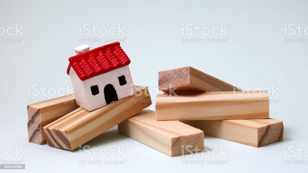 A miniature house and wooden blocks. stock photo