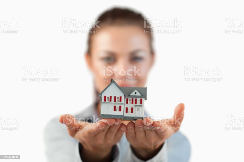 Miniature house being shown by female estate agent stock photo