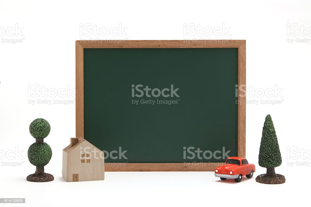 Miniature house, car, and blackboard on white background. stock photo