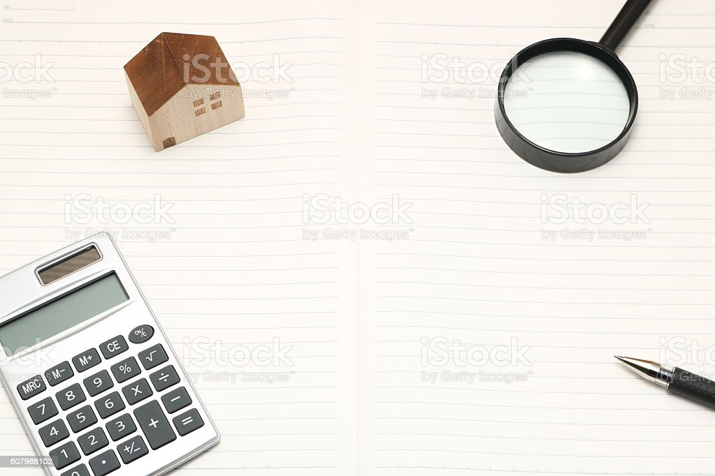Miniature house, magnifying glass, calculator, pen, and notebook. stock photo