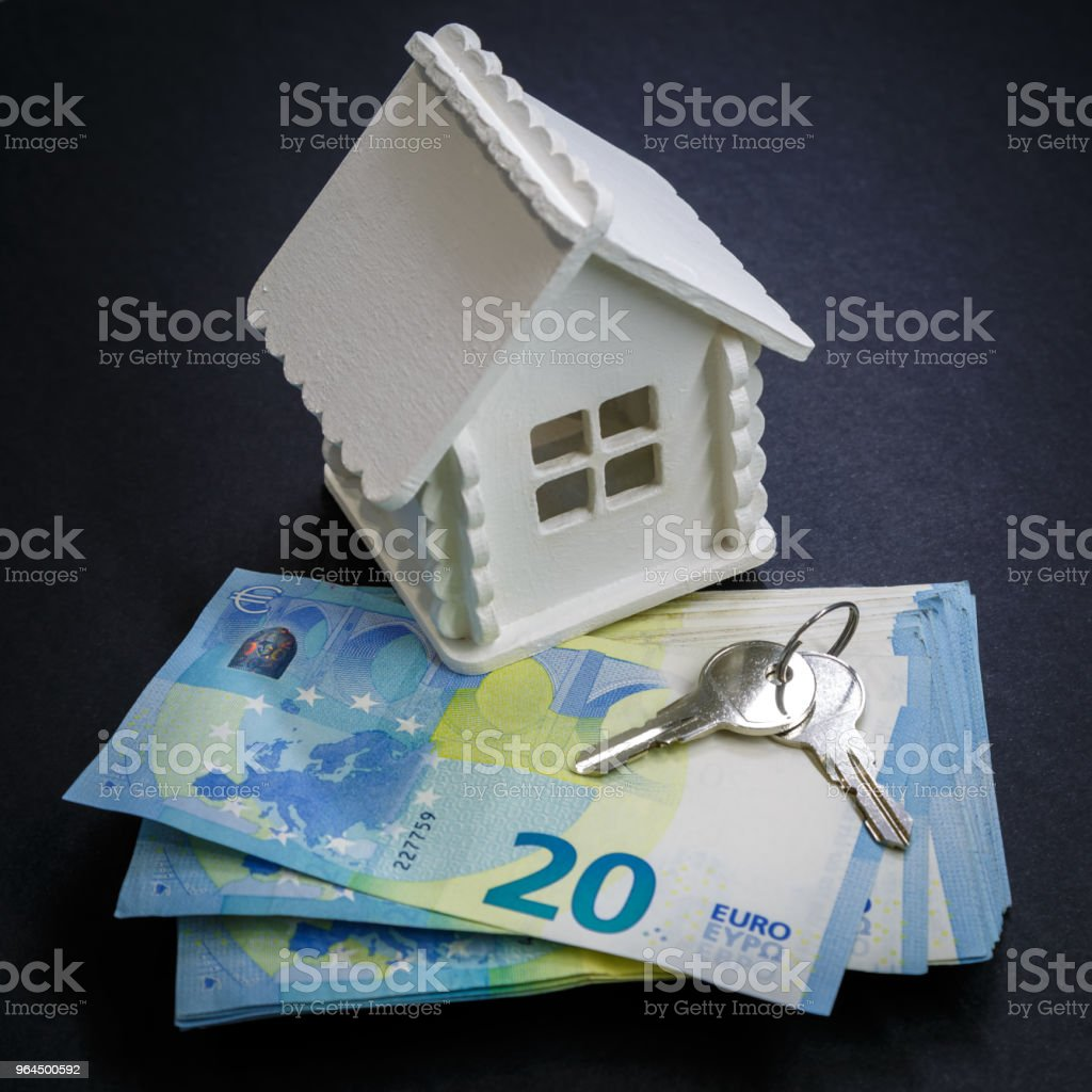 Miniature house of white colour, money and keys as an illustration of the process of buying a home stock photo