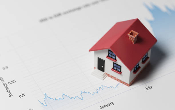 miniature house on a blue financial graph - interest rate stock photos and pictures
