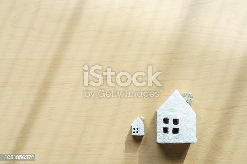 885968454istockphoto Miniature house on wooden background 1081856372