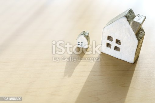 885968454istockphoto Miniature house on wooden background 1081856390