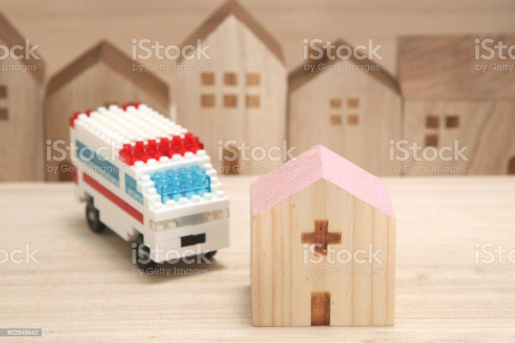 Miniature houses, hospital and ambulance on white background. stock photo
