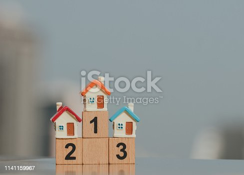 istock Miniature houses on wooden block number one two three using as business and property concept. 1141159967