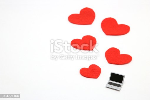 istock Miniature laptop and some red hearts on white background. 924724106