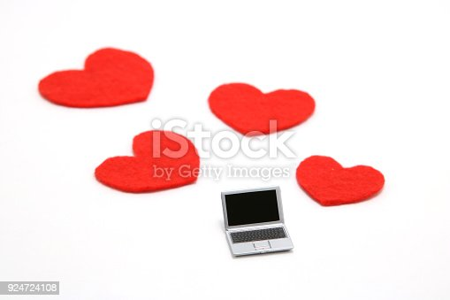 istock Miniature laptop and some red hearts on white background. 924724108