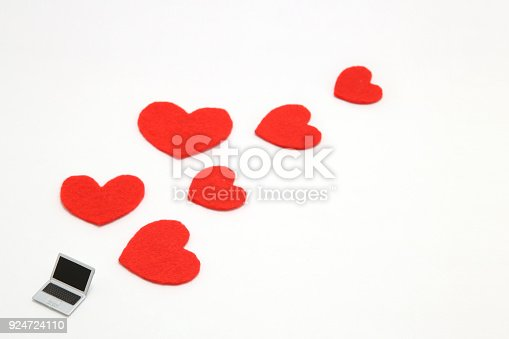 istock Miniature laptop and some red hearts on white background. 924724110