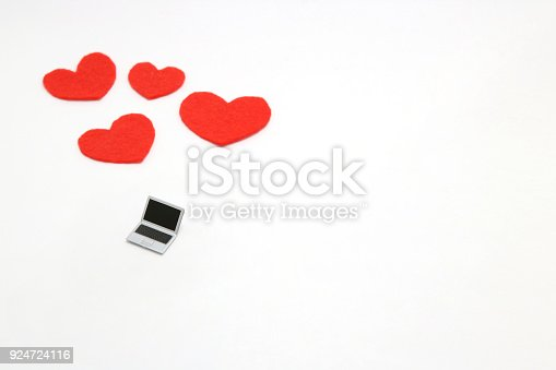 istock Miniature laptop and some red hearts on white background. 924724116