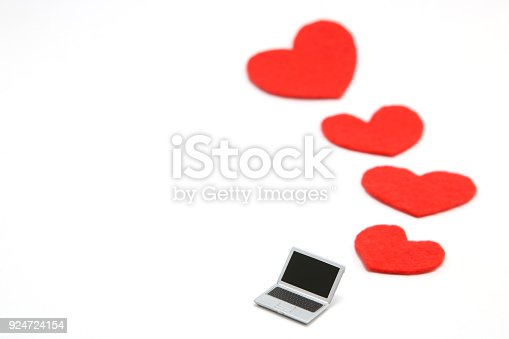 istock Miniature laptop and some red hearts on white background. 924724154