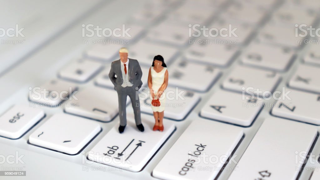 A miniature man and a miniature woman standing at the Tab Key. stock photo