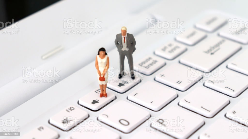 A miniature man and a miniature woman standing on a different volume keyboard. The concept of social disparity between men and women. stock photo