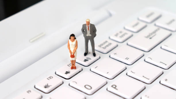 A miniature man and a miniature woman standing on a different volume keyboard. The concept of social disparity between men and women. A miniature man and a miniature woman standing on a different volume keyboard. The concept of social disparity between men and women. discriminatory stock pictures, royalty-free photos & images
