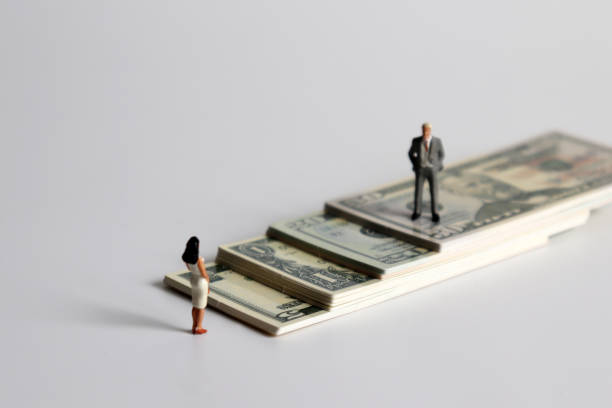 a miniature man and a miniature woman standing on a pile of bills. - gender stereotypes stock pictures, royalty-free photos & images