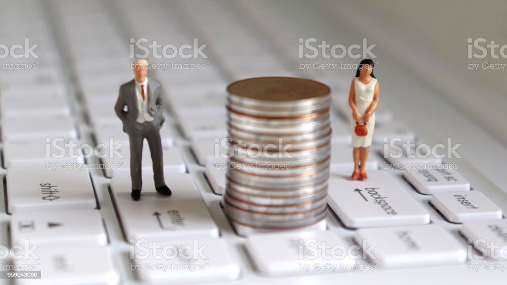 A miniature man and a miniature woman standing on top of the keyboard with a pile of coins in the middle. stock photo