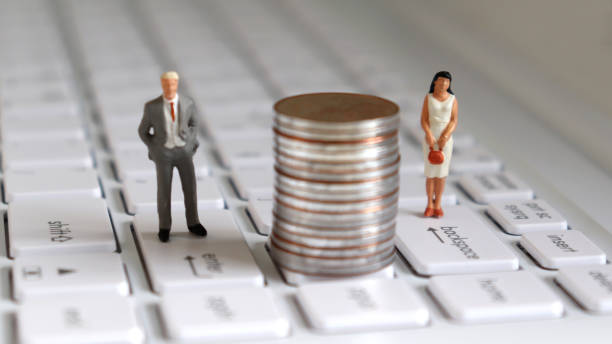 A miniature man and a miniature woman standing on top of the keyboard with a pile of coins in the middle. A miniature man and a miniature woman standing on top of the keyboard with a pile of coins in the middle. discriminatory stock pictures, royalty-free photos & images