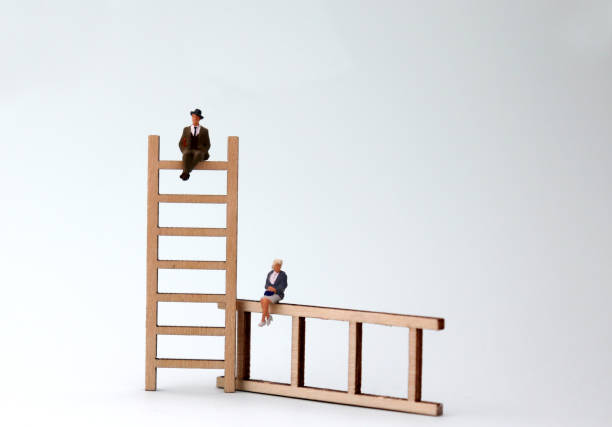 A miniature man and woman sitting on a wooden ladder. The concept of gender inequality in promotion. A miniature man and woman sitting on a wooden ladder. The concept of gender inequality in promotion. discriminatory stock pictures, royalty-free photos & images
