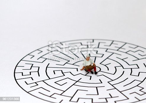 istock A miniature man sitting in the middle of a maze with a white background. 961201366