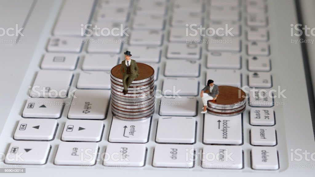 A miniature man sitting on a stack of coins on the Enter key and a miniature woman sitting on a stack of coins on the Backspace key. Theconceptofagenderpromotiongap. stock photo