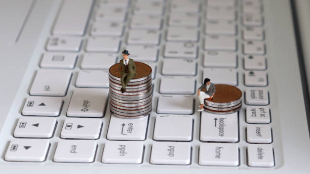 A miniature man sitting on a stack of coins on the Enter key and a miniature woman sitting on a stack of coins on the Backspace key. Theconceptofagenderpromotiongap. A miniature man sitting on a stack of coins on the Enter key and a miniature woman sitting on a stack of coins on the Backspace key. Theconceptofagenderpromotiongap. discriminatory stock pictures, royalty-free photos & images