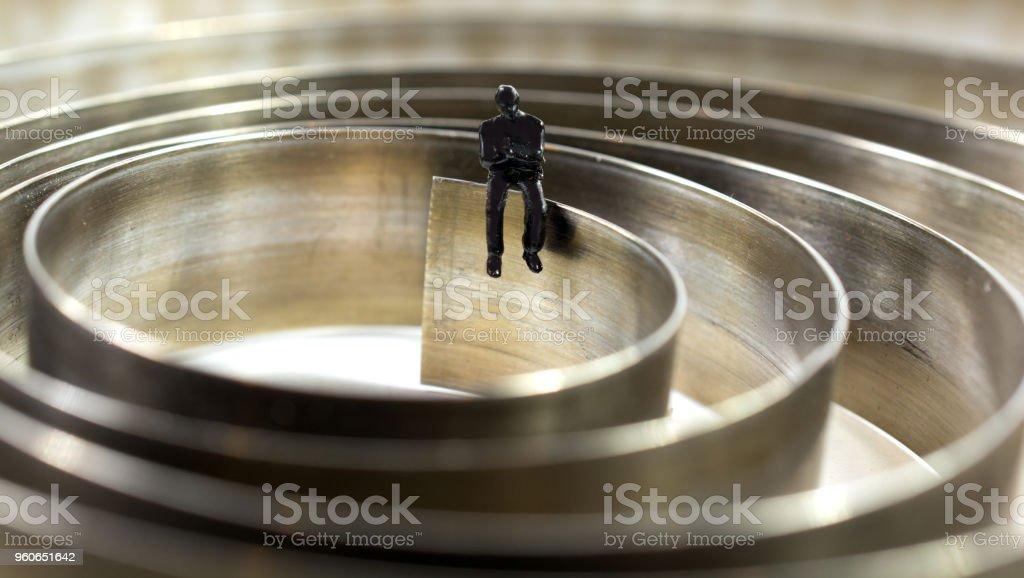 Miniature man sitting on large clock spring stock photo